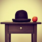 picture of a bowler hat and an apple on a bureau, homage to Rene Magritte painting The Son of Man, w