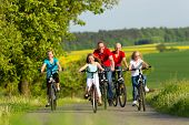 stock photo of bike path  - Family with three girls having a weekend excursion on their bikes or bicycles on a summer day in beautiful landscape - JPG