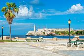 Romantic park in Havana with a view of the castle and lighthouse of El Morro at the bay entrance