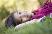 Photo of little girl lying on grass.