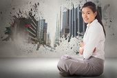 Businesswoman sitting cross legged with arms crossed against splash showing cityscape