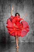 dancer in red dress posing on studio background