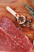 raw beef meat fillet with peppercorn and thyme ready to grill on wood board isolated over white back