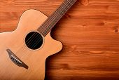 Close-up western guitar on brown wooden background poster