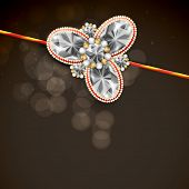 stock photo of rakhi  - Shiny diamonds decorated rakhi on brown background for Hindu community festival Raksha Bandhan celebrations - JPG