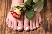 Female feet with spa pedicure and rose