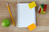 A blank notebook, green apple, pencil, measuring tape on wooden background