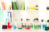 Different laboratory glassware with color liquid on laboratory background