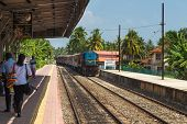 HIKKADUWA, SRI LANKA - MARCH 12, 2014: Train approaching Hikkaduwa train station. Trains are very ch