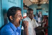 HIKKADUWA, SRI LANKA - MARCH 12, 2014: Local man yawning in train. Trains are very cheap and poorly