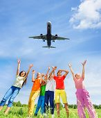 Excited children with hands up to plane in sky