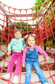 Two charming girls on net of playground