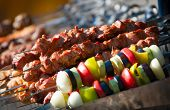 Prepared shashlik, lamb meat grilling on metal skewer and grilled vegetables