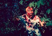 Man zombie walking dead outdoors. Dark lighting. Color was changed to emphasize the atmosphere of ho