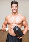 image of muscle builder  - Portrait of a shirtless body builder holding a scoop of protein mix in gym - JPG