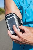Athletic man adjusting his music player on a run on a sunny day