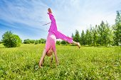 image of upside  - Girl making flip on grass standing upside down outside in summer - JPG