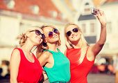 holidays, tourism and modern technology concept - three beautiful girls taking picture with digital