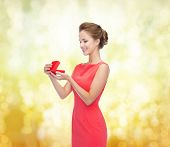 christmas, holiday, valentine's day and celebration concept - smiling young woman in red dress with
