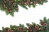 Traditional natural christmas background border with mistletoe, spruce fir and pine cones over white with copy space.