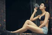 Beauty Retro Woman Smoking Cigarette And Sitting On Windowsill