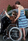A Disabled Elderly Woman Getting Into A Car
