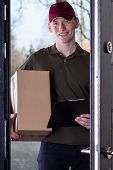 Courier With Order Standing In Door