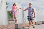 Young man and woman in love promenade near fountains