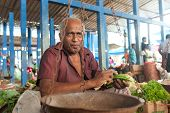 HIKKADUWA, SRI LANKA - FEBRUARY 23, 2014: Portrait of vendor selling vegetables. The Sunday market is great way to see Hikkaduwa's local life come alive along with fresh produce and local delicacy