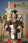 Portrait of Roman centurion holding sword with ancient buildings in background