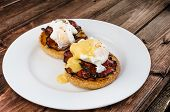 image of benediction  - Benedict eggs with crispy bacon and hollandaise sauce on toasted Maffin on clean plate - JPG