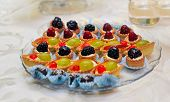 Set of tasty mini cakes with raspberries, blackberries, cranberries, blueberries and grapes