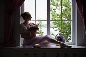 Ballet dancer sitting on windowsill holding flowers