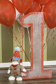 image of sock-monkey  - A sock monkey and wooden number one sign with balloons attached - JPG