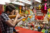 Young fun couple playing shooting games at amusement park