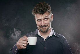 picture of sarcastic  - handsome bearded man stands in fog with cup of coffee in his hand and looks at camera - JPG