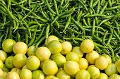 Fresh Green Chili Peppers And Lemons In Asian Market