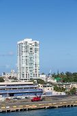 stock photo of san juan puerto rico  - A red construction crane in front of a San Juan Puerto Rico high rise condo building - JPG