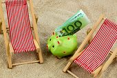 beach chair with euro currency on the sandy beach. symbolic photo for cost of travel, vacation, holidays