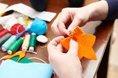 Process of hand made soft toys sewing with felt and needle for Christmas tree decoration