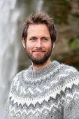 Portrait of man in Icelandic sweater outdoor smiling by waterfall on Iceland. Portrait of good looking bearded male model in nature.