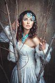 pic of faerie  - Girl standing among the branches her white dress - JPG