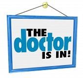 The Doctor Is In words on a hanging office window sign to advertise the physician or medical practicioner is ready for your check-up, physical or appointment