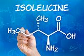 Hand with pen drawing the chemical formula of isoleucine