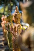 Clay praying women statue in the buddhist temple in Thailand