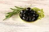 Black olives in small plate with branch on painted wooden background