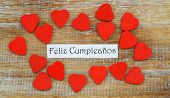 Feliz Cumpleanos (which means Happy Birthday in Spanish) with little red wooden hearts