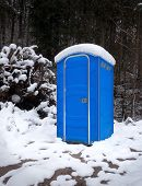 Snowy portable toilet in the forest