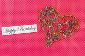 Happy Birthday card with heart made of colorful beads on pink dotty background