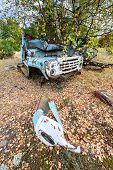 stock photo of junk-yard  - rusty wreck on junk yard near Illinci village in Chernobyl Nuclear Power Plant Zone of Alienation Ukraine - JPG